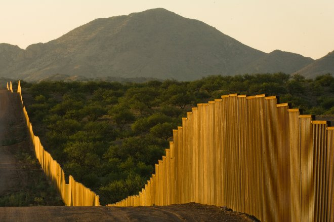 The border fence between Arizona and Mexico glistens in the morning sunlight.